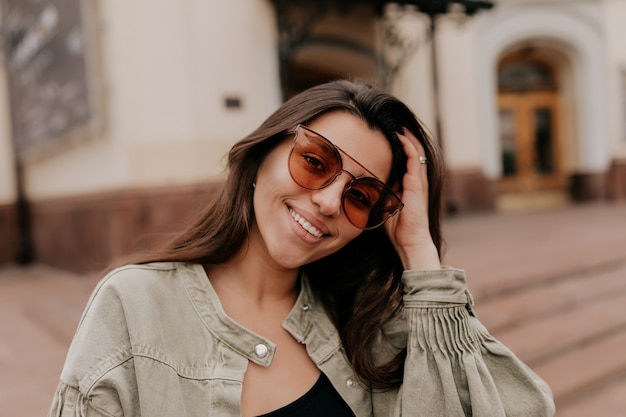 Schließen sie herauf außenporträt der reizenden attraktiven frau, die sonnenbrillen trägt, die auf frühlingsstadt lächeln und gehen