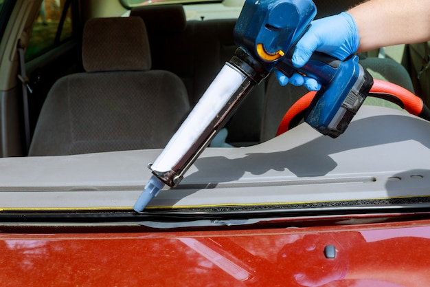 Schließen sie herauf autoglasurarbeitskraft-silikonkleber eine windschutzscheibe eines autos an einer tankstelle.