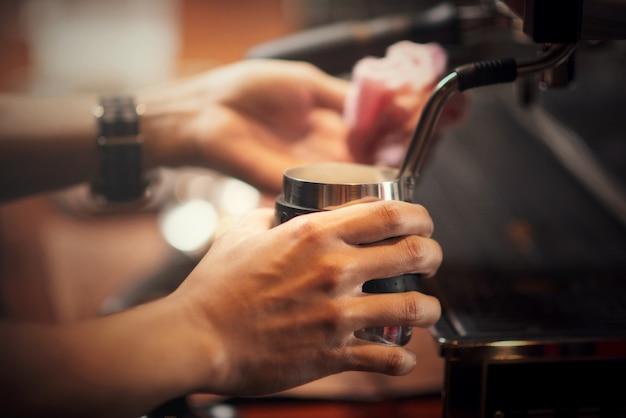 Schließen sie herauf barista, der cappuccino, der barmixer macht, der kaffeegetränk zubereitet