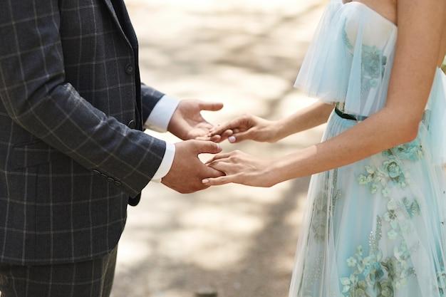 Schließen sie herauf beschnittenes foto von zwei jungen liebhabern, die hände halten