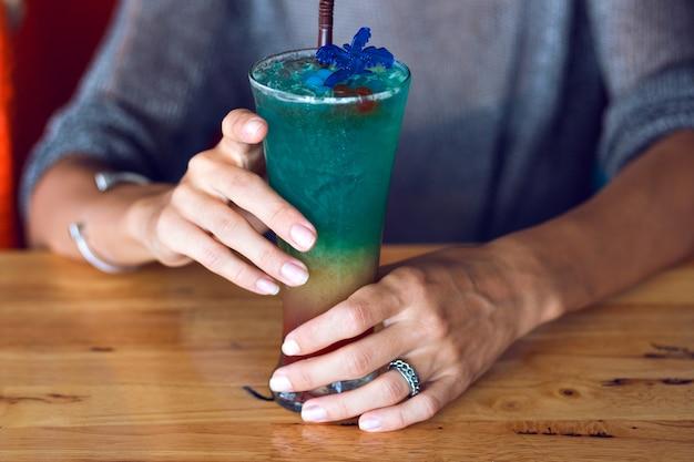 Schließen sie herauf bild der frau, die leckeren bunten regenbogengeschmackvollen alkoholischen süßen cocktail hält, sommerfestzeit.