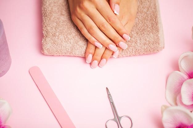 Schließen sie herauf bild der frau, die nagelpuffer verwendet, wenn sie maniküre machen, nägel zu hause polierend.