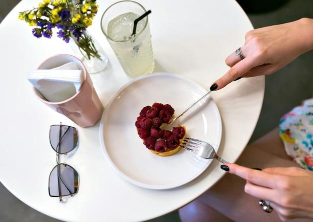 Schließen sie herauf bild der frauenhände, die den leckeren himbeerkuchen, das cafébild, die elegante maniküre, die weichen getönten farben schneiden, genießen sie nachtisch, diäternährungskonzept.
