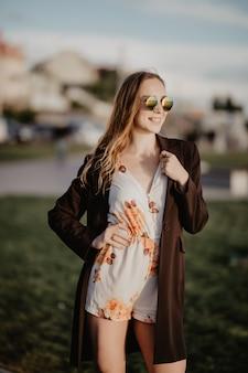 Schließen sie herauf bild der glücklichen frau in der sonnenbrillenkleidung, die seitlich im freien aufwirft