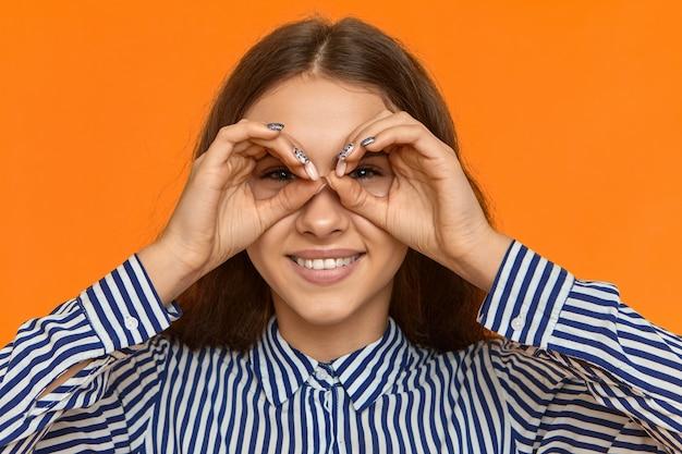 Schließen sie herauf bild der glücklichen fröhlichen jungen kaukasischen frau, die stilvolles gestreiftes hemd trägt