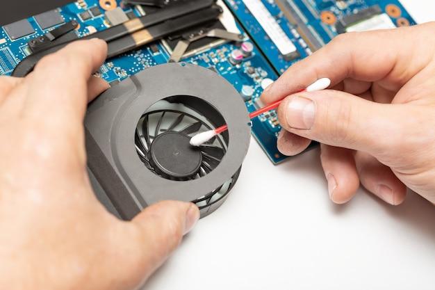 Schließen sie herauf bild der männlichen technikeringenieurhand, die den staub vom laptop-lüfter nahe der leiterplatte mit einem wattestäbchen reinigt.