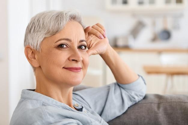 Schließen sie herauf bild der modischen eleganten älteren frau mit stilvollem haarschnitt und machen sie das entspannen drinnen, bequemes sitzen auf couch mit hand auf ihrem gesicht, mit sorglosem lächeln schauend