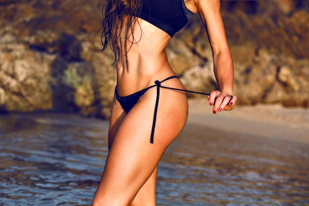 Schließen sie herauf bild der sexy atemberaubenden frau, die auf dem strand bei sonnenuntergang, getönten farben, gesundem fitnesslebensstil aufwirft.