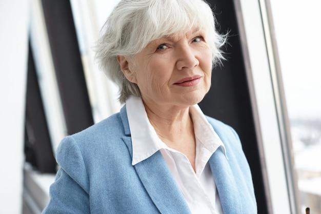 Schließen sie herauf bild der stilvollen ordentlichen rentnerin mittleren alters mit falten, grauem haar und natürlichem make-up, das am fenster während der kaffeepause während des arbeitstages im büro steht und schaut