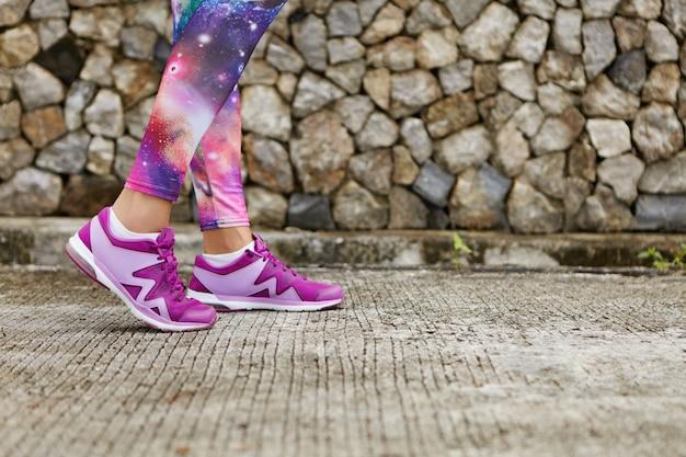 Schließen sie herauf bild der violetten weiblichen laufschuhe während des trainings im freien. beschnittenes porträt der sportlerin, die auf gekacheltem pflaster joggt, das sportbekleidung des kosmischen drucks trägt.
