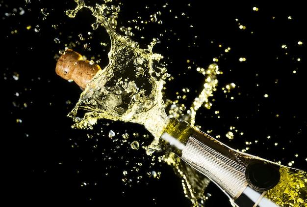 Schließen sie herauf bild des champagnerkorkens fliegend aus champagnerflasche heraus