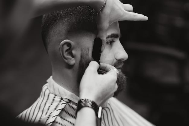 Schließen sie herauf bild des friseurs, der einen mann mit einem scharfen stahlrasierer rasiert.