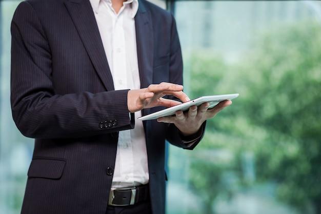 Schließen sie herauf bild des geschäftsmannes, der eine digitale tablette hält, porträt des hübschen jungen mannes, der mit tablette im büro arbeitet. intellektueller und sicherer geschäftsmann, der touchpad mit infografiken hält