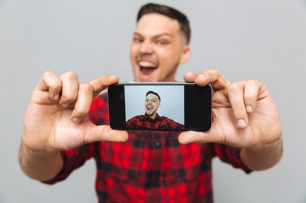 Schließen sie herauf bild des glücklichen mannes, der foto auf smartphone macht