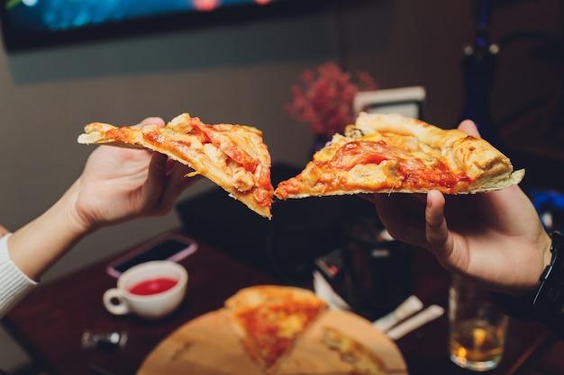 Schließen sie herauf bild einer weiblichen hände, die ein stück pizza halten.