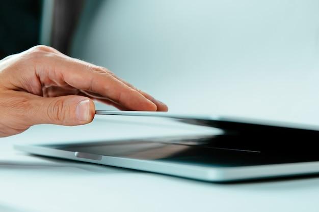 Schließen sie herauf bild eines mannes, der die abdeckung seines laptops öffnet