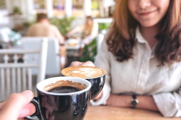 Schließen sie herauf bild eines mannes und einer frau, die zwei kaffeetassen auf holztisch im café klirren