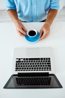 Schließen sie herauf bild von den händen des jungen geschäftsmannes, die am tisch sitzen und am laptop arbeiten kaffeetasse halten. weiße moderne büroeinrichtung