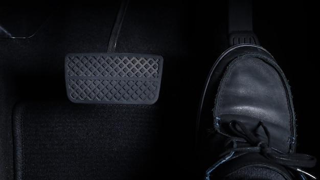 Schließen sie herauf bilder des mannes, der auto fährt, indem sie gaspedal und bremspedal mit schwarzem lederschuh des rechten fußes und schwarzer jeanshose drücken. im japanischen auto.