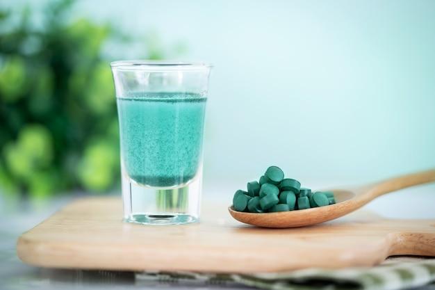 Schließen sie herauf blaue spirulina smoothie- und spirulinapillen des strengen vegetariers, eine gesunde superfood-diät und ein detoxnahrungskonzept