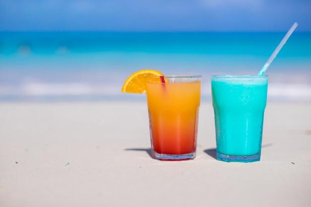 Schließen sie herauf blaues curaçao und mangococktail auf dem weißen sandigen strand