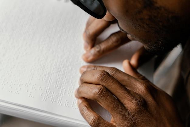 Schließen sie herauf blinder mann, der blindenschrift liest