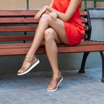 Schließen sie herauf bloße muskulöse frauenbeine im kurzen roten kleid, das auf holzbank sitzt