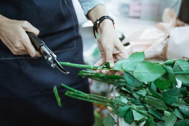 Schließen sie herauf blumenladenfrauenhandblumenstielschnitt, der im blumenladen arbeitet