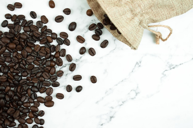 Schließen sie herauf braune kaffeebohnen in einer stofftasche auf einer marmortabelle mit kopienraum, draufsicht.