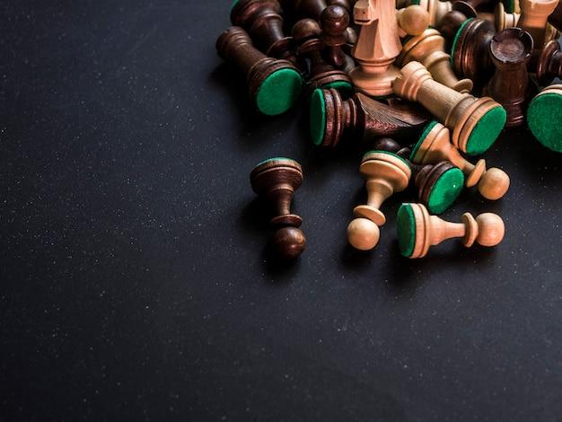 Schließen sie herauf bündel klassische traditionelle schachfiguren auf schwarzer oberfläche
