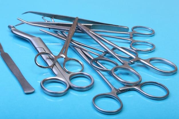 Schließen sie herauf chirurgische instrumente und werkzeuge auf blauem spiegel.