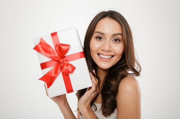 Schließen sie herauf das foto der netten frau geschenk-eingewickelten kasten mit rotem bogen auf der kamera zeigend, die das glück und freude ausdrückt, lokalisiert über weiß