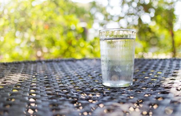 Schließen sie herauf das gereinigte frische getränk in einem glaswasser von der flasche auf tabelle im garten.