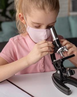 Schließen sie herauf, das kind mit mikroskop lernt