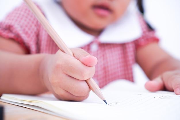 Schließen sie herauf das kleine kind, das lernt, auf papier zu schreiben.