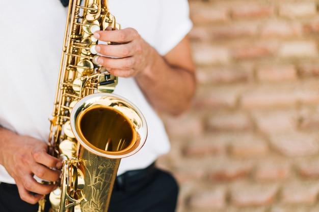 Schließen sie herauf das saxophon, das vom mann gespielt wird