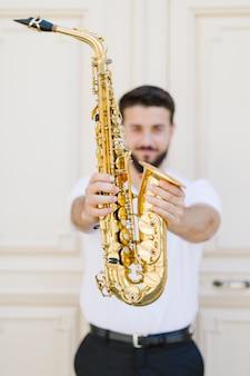 Schließen sie herauf das saxophon, das vom musiker gehalten wird