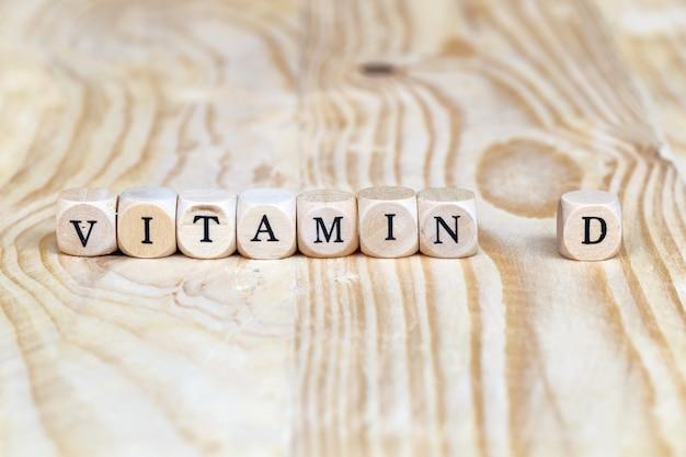 Schließen sie herauf das wort des vitamins d, das auf dem tisch von den hölzernen buchstaben, gesundheitskonzept gemacht wird