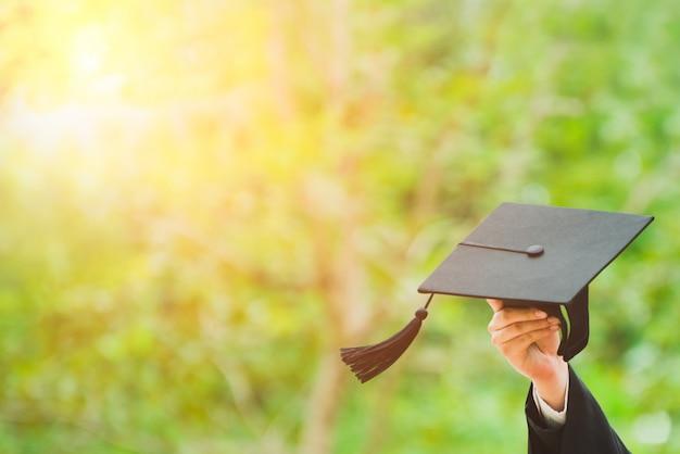 Schließen sie herauf den absolvent, der einen hut hält. konzept erfolg ausbildung an der universität