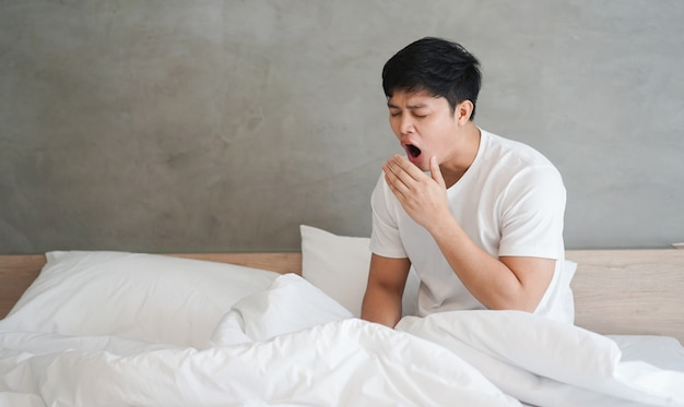 Schließen sie herauf den asiatischen mann, der am schlafzimmer am ferientag aufwacht und gähnt