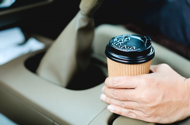 Schließen sie herauf den fahrer, der einen tasse kaffee im auto hält.