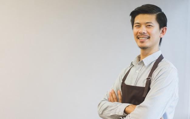Schließen sie herauf den gekreuzten arm des asiatischen mannes barista auf hintergrund, kmu-geschäftskonzept