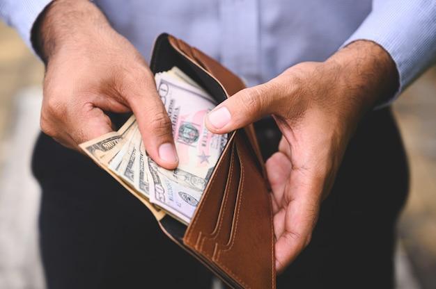 Schließen sie herauf den geschäftsmann, der die geldverbreitung des bargeldes in der geldbörse zählt.