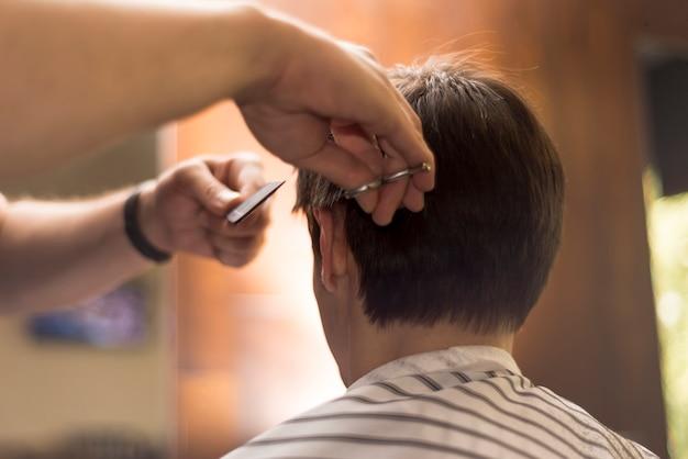 Schließen sie herauf den hinteren ansichtmann, der einen haarschnitt erhält