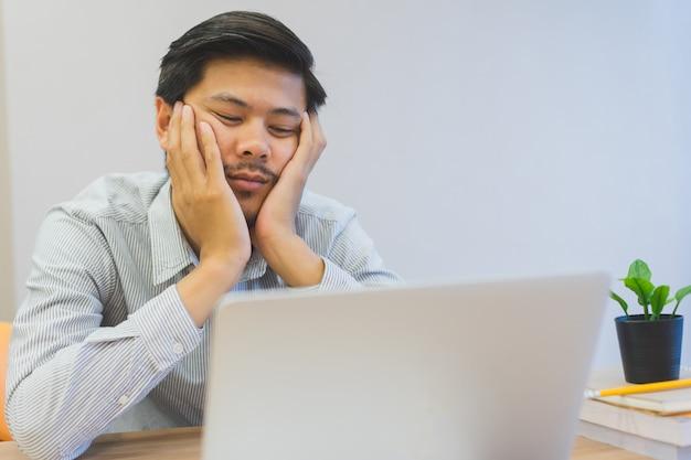 Schließen sie herauf den jungen asiatischen mann, der am schreibtisch, lebensstilkonzept gelangweilt und schläfrig sich fühlt