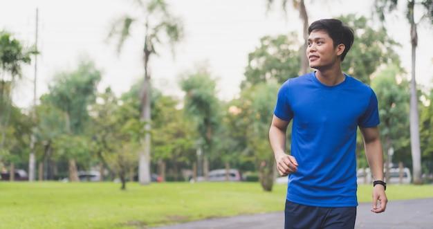 Schließen sie herauf den jungen asiatischen mann, der morgens park am im freien läuft
