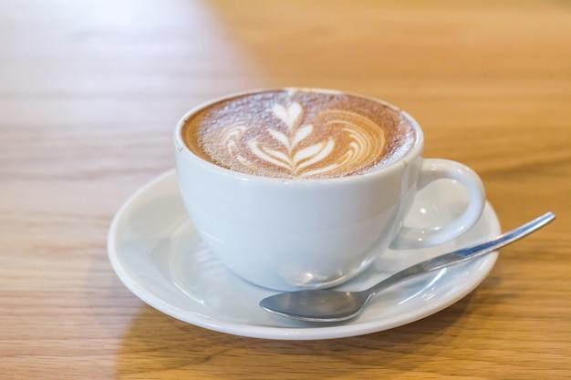 Schließen sie herauf den lattekaffee und weiße kaffeetasse, die auf holzfußböden gesetzt werden