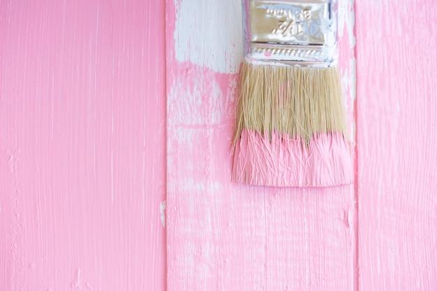 Schließen sie herauf den malerpinsel, der rosa farbe auf einem weißen holztisch malt.