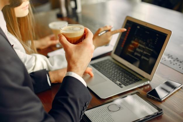 Schließen sie herauf den mann, der mit einem laptop am tisch arbeitet
