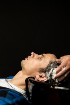 Schließen sie herauf den mann, der mit kopienraum hairwashed erhält